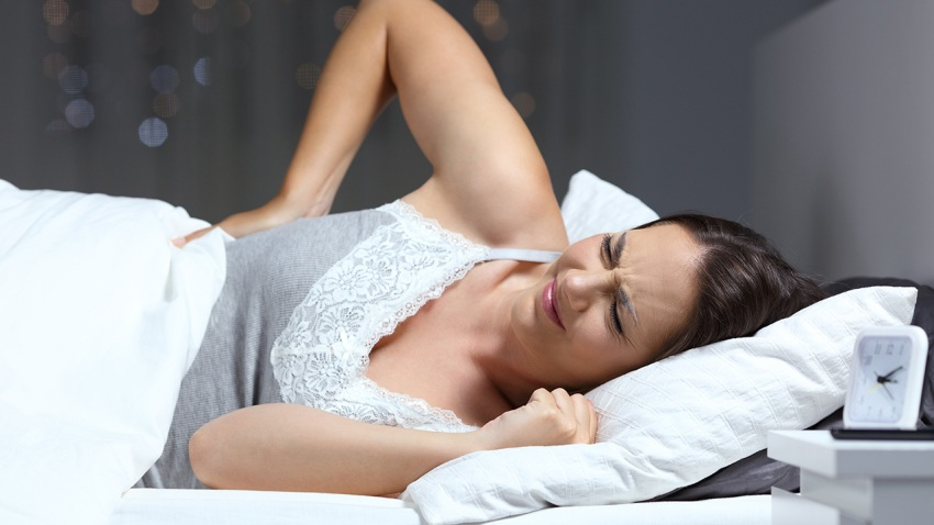 Woman suffering back ache on the bed in the night