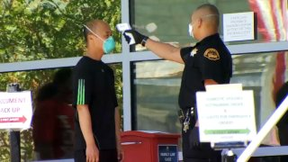 A person undergoes a temperature check outside a Contra Costa County court building.