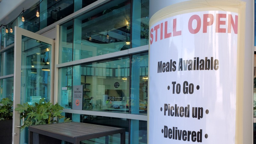 Sign on facade at a restaurant announcing that the restaurant would remain open for takeout orders during an outbreak of the COVID-19 coronavirus.