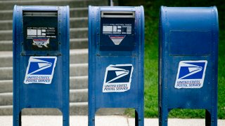 In this May 9, 2013, file photo, U.S. Postal Service (USPS) mailboxes stand in Washington, D.C.
