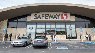 Customers, some wearing protective masks and gloves, wait in a line outside a a Safeway store.