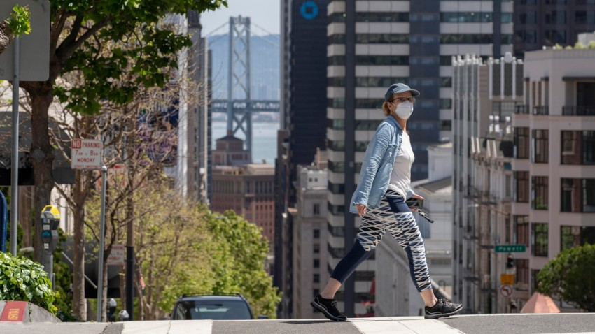 A pedestrian wearing a face masks crosses an empty street amid the coronavirus outbreak in San Francisco.