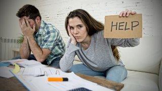 """Mujer sostiene cartel que dice """"Ayuda' y hombre se lleva las manos al rostro frente a papeles y calculadora."""