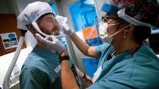 Enfermeros se desinfectan las máscaras protectoras después de tener contacto con un paciente con COVID-19.