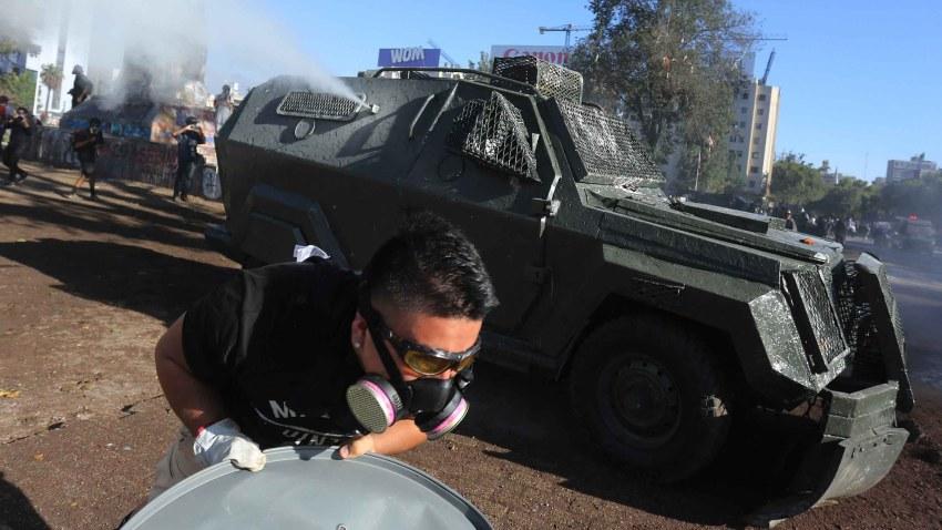 Un grupo de personas se enfrenta a la policía antidisturbios, este viernes, en la Plaza Italia en Santiago de Chile durante una nueva jornada de protestas.