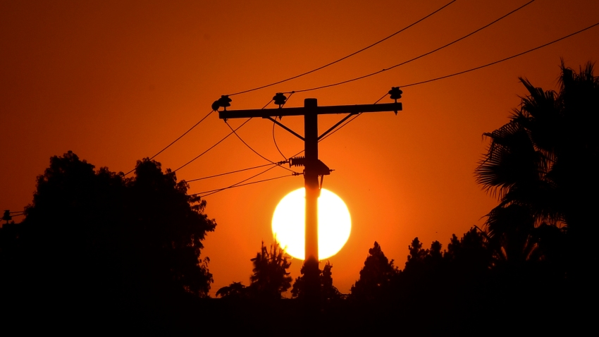 In this Sept. 3, 2020, file photo, the sun sets behind power lines in Los Angeles, California, ahead of a heatwave.