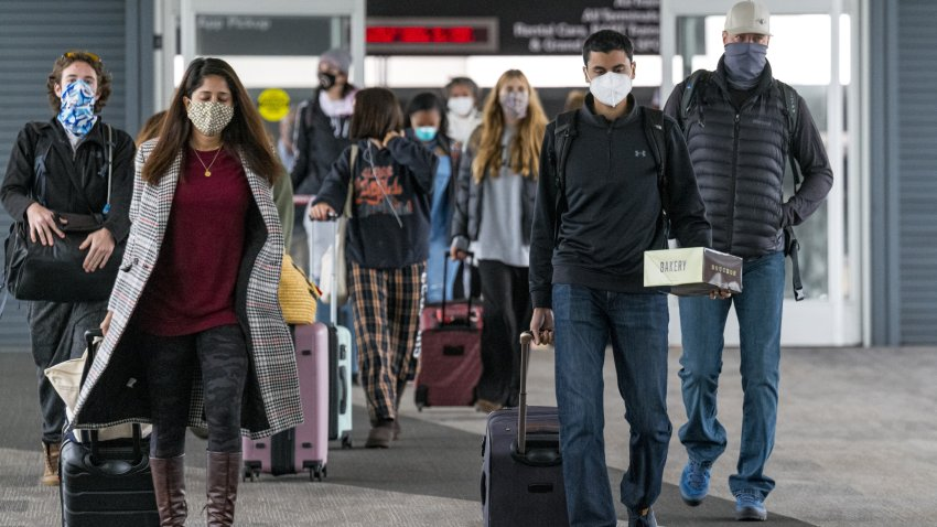 Travelers wearing protective masks arrive at San Francisco International Airport (SFO) in San Francisco, California, on Monday, Nov. 24, 2020. Airlines set a new post-pandemic record for U.S. passengers on Sunday as the Thanksgiving holiday spurred travel despite government warnings.