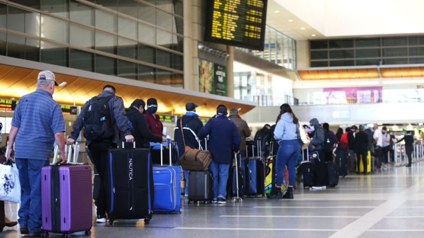 Travelers wait in line to check in for a flight