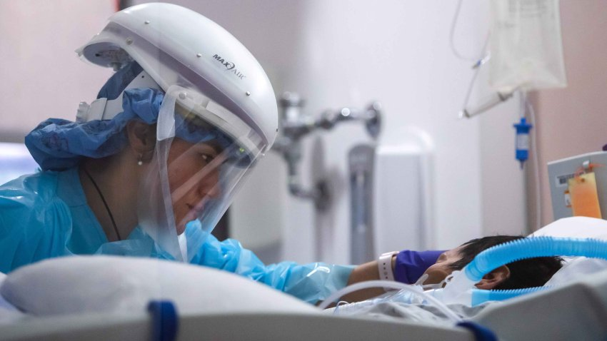 In this Jan. 3, 2021, file photo, registered nurse Yeni Sandoval wears personal protective equipment (PPE) while she cares for a COVID-19 patient in the Intensive Care Unit (ICU) at Providence Cedars-Sinai Tarzana Medical Center in Tarzana, California.