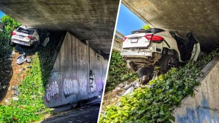 A Maserati wedged between an embankment and a freeway underside.