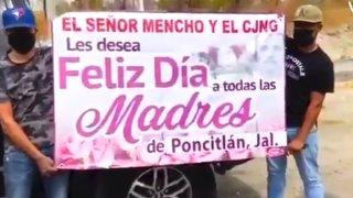 Dos hombres con el rostro cubierto sostienen una manta en el que el Cártel Jalisco supuestamente felicita a las madres