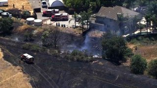 Firefighters work at the scene of a fire in the Morgan Hill area.
