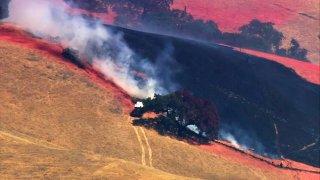 Firefighters battle a fire near Morgan Hill.