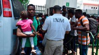 Un grupo de migrantes junto a una camioneta aguardan para ingresar a una sede migratoria en México, donde deberán demostrar su estancia legal en el país.
