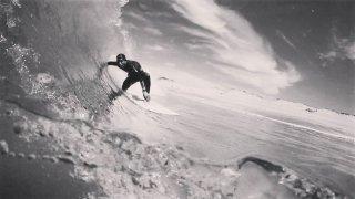 El surfista español Óscar Serra entre una enorme ola en una fotografía en blanco y negro