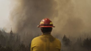 A firefighter watches fire burning through trees during the Caldor Fire in Kirkwood, California, U.S., on Friday, Sept. 3, 2021. The Caldor Fire, which ignited Aug. 14 has burned at least 212,907 acres, or more than 332 square miles, and containment stood at 29% as of Friday, Cal Fire said in its morning update. Photographer: Eric Thayer/Bloomberg via Getty Images
