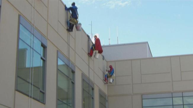 Superhéroes limpian ventanas en el UCSF Benioff